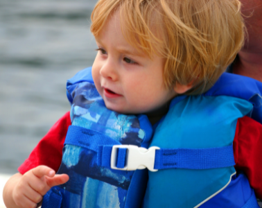 Young child in blue life jacket.