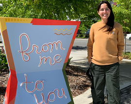 """Artist, Tina Velazquez Hays, with her piece, """"From me to you (from you to me)"""" at Downtown Park"""