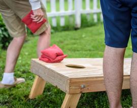 Two people playing cornhole