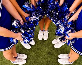 A group of cheerleaders circled up