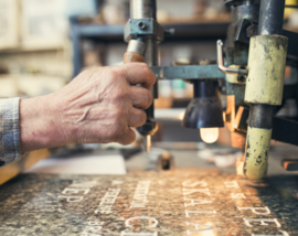 Close up picture of a person engraving a stone paver