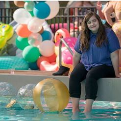 Aidy Bryant sitting by a pool in the Hulu show Shrill