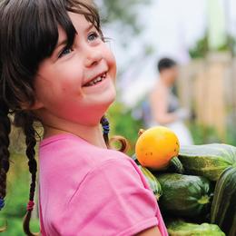 smiling child in garden, holding vegetables