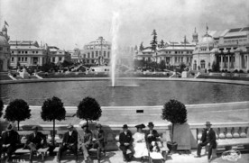 Historic scene of fairgoers sitting around the edge of a fountain at the 1909 Alaska Yukon Pacific Exposition, Seattle's first world's fair.