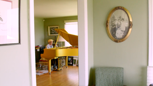 Deems Tsutakawa plays piano in his home.