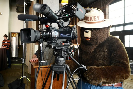 Smokey Bear mascot stands behind the camera at a taping of Civic Cocktail.