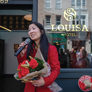 Tanya Woo holding bouquet of flowers and speaking in front of the new Louisa Hotel