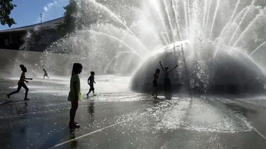 Children play in the spray of the Seattle International Fountain.