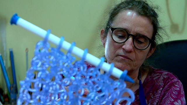 Artist Carol Milne works on one of her knitted glass sculptures.