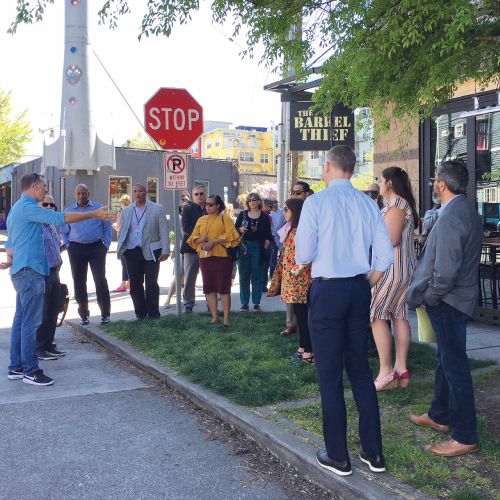 dozen people standing on a street corner discussing community issues
