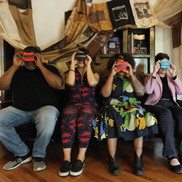 four people sitting in chairs looking through viewfinders