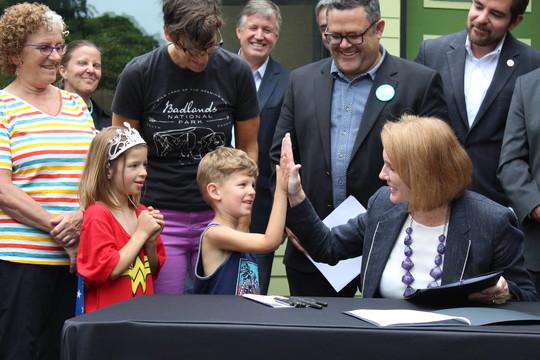 Mayor Durkan high-fives a young boy after signing ADU/DADU legislation