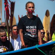 Young woman, with red painted hand print over her mouth, standing in a Cowlitz tribal canoe