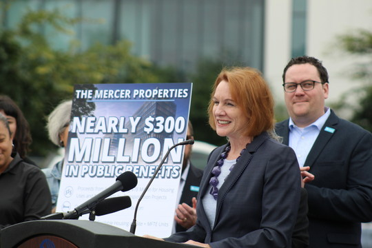 "Mayor Jenny Durkan speaking at the Mercer Properties press conference with sign in the background reading ""Nearly $300 million in public benefits."""