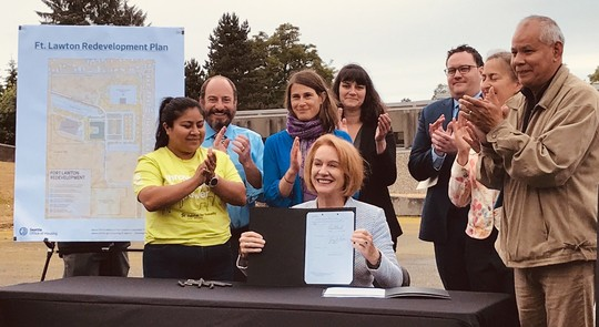 Mayor Durkan holds up the signed legislation creating more affordable housing at Fort Lawton