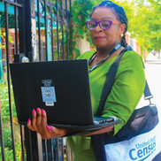 census canvasser with laptop computer, waiting outside a residence