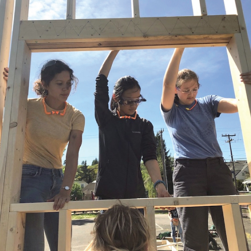 3 young women holding up the wooden frame of a wall