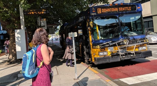 Photo of a woman waiting for the E line bus in downtown Seattle