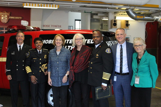 Mayor Durkan poses with Councilwoman Bagshaw, Chief Best, Chief Scoggins, HSD Director Jason Johnson and others in front of a Health One vehicle