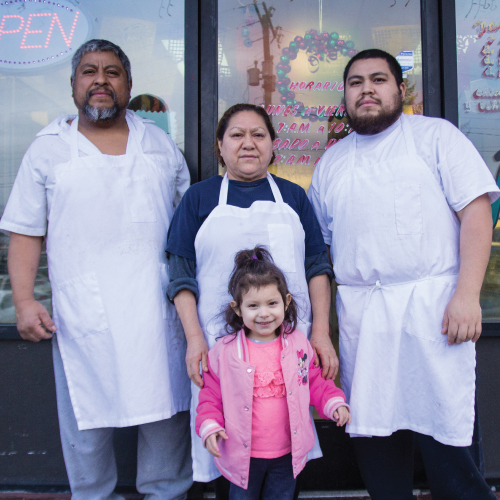 3 adults and one child standing in front of their restaurant doorfront