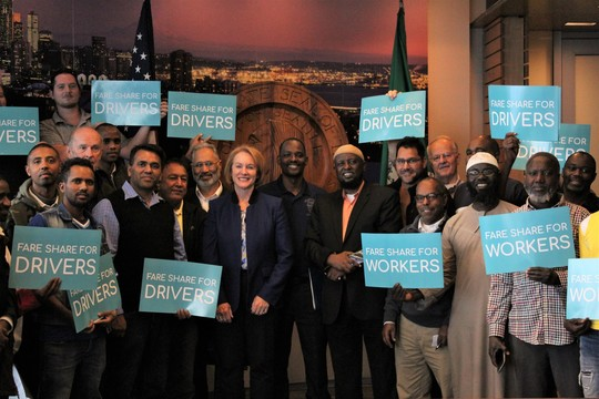 Mayor Durkan stands with drivers who support her Fare Share plan in the Norman B. Rice room, Seattle City Hall