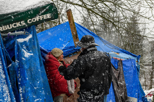 A member of the Seattle Navigation team encourages a man bundled up in blankets and coats to come inside during the February 2019 snowstorm