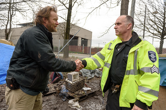 Sgt. Zerr from the Seattle Navigation Team and a man experiencing homelessness shake hands during an encampment visit