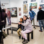 woman sitting with child on a bench looking at a museum exhibit