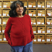 Dorothy Cordova, standing in front of archive boxes