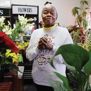 Mary Wesley, standing in her flower shop