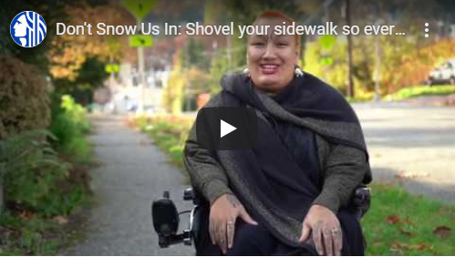 Screenshot of Rooted in Rights video with a smiling, red-haired woman seated in a powered wheelchair.