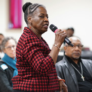 African-American woman speaking into microphone at public event
