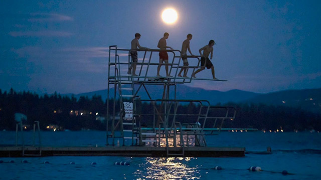 Swimmers jump off a diving board under a full moon.