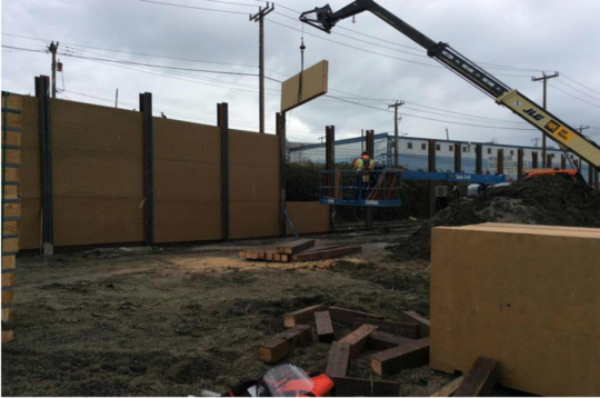 Crews install plywood as part of the screen wall.