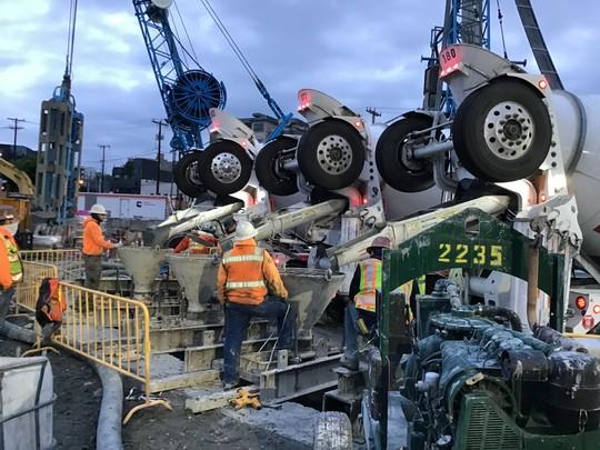 Trucks pour concrete into slurry wall panel.