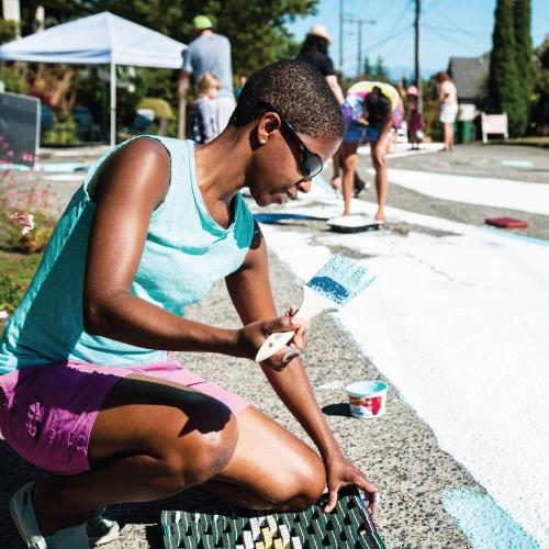 woman painting street mural