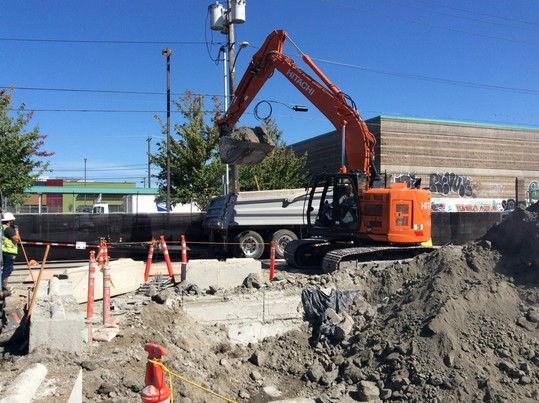 Excess grout and soil is loaded onto trucks to be hauled away in East Ballard