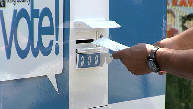 A voter puts their ballot into a ballot box