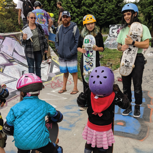 Teens and younger kids stand in a group with skateboards