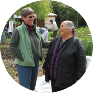 Two women smiling and chatting in a community garden