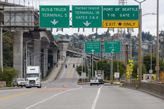 Photo of the east entrance to the West Seattle Low Bridge. Trucks and cars are shown both driving away from the direction of the camera and coming towards the direction of the camera.
