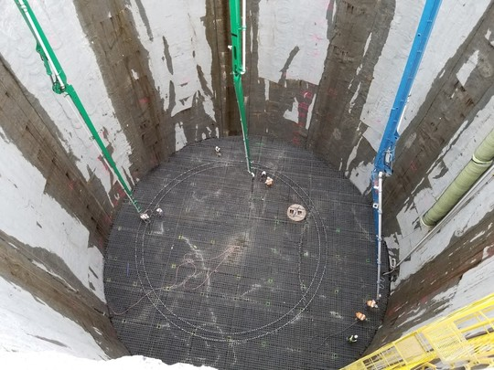 Photo showing concrete being poured into the Ballard vertical shaft to form the floor.