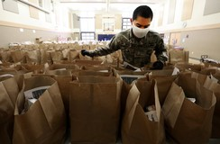 A volunteer loads meal deliver bags to be delivered from Asian Counseling and Referral Services