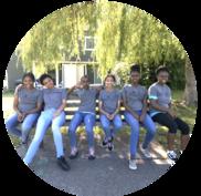 Six teenage girls sitting on bench, smiling at camera