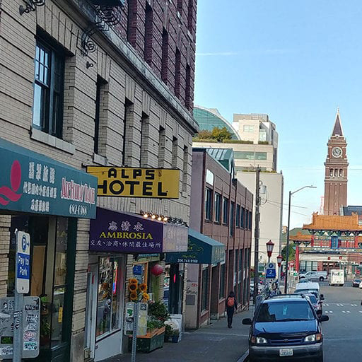 View down a city street in Chinatown International District with a clocktower in the distance