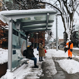 Two people waiting at a bus stop on a snowy street while a city worker in orange gear shovels the sidewalk.