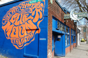 Image of the outside of a bar with a blue and orange mural painting that says Blue Moon Tavern