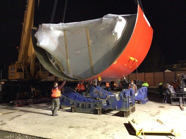 Photo showing the lower shield of the tunnel boring machine being unloaded in Ballard.