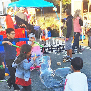 Street fair with children playing and blowing bubbles, a large chest game, and people mingling