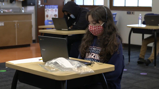 Students learn while masked in a classroom.